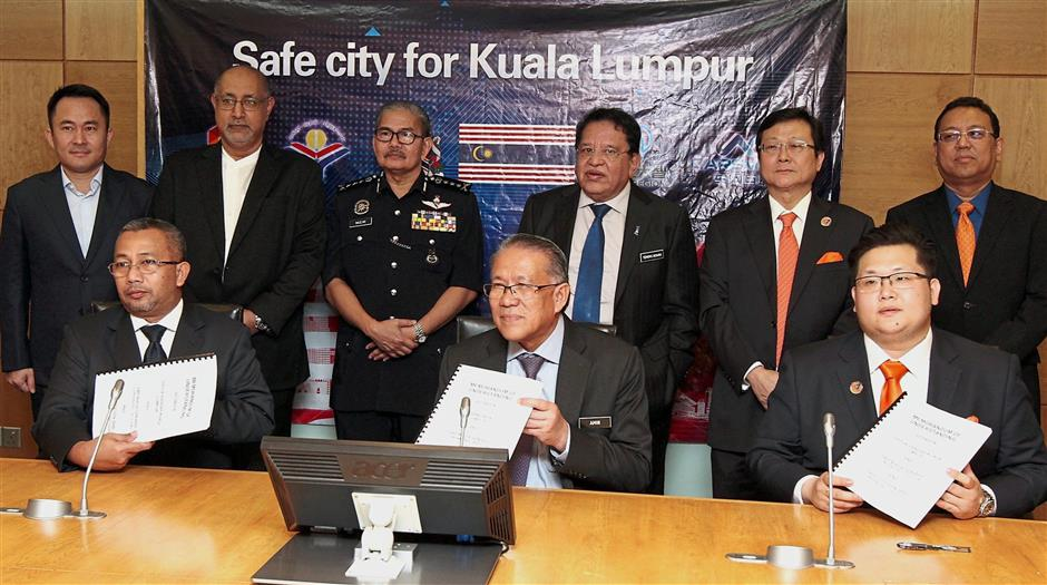 (Seated from left) Roslan, Amin Nordin, and Tan with the signed memorandum at Menara DBKL as Tengku Adnan (standing third from right) and other VIPs look on.