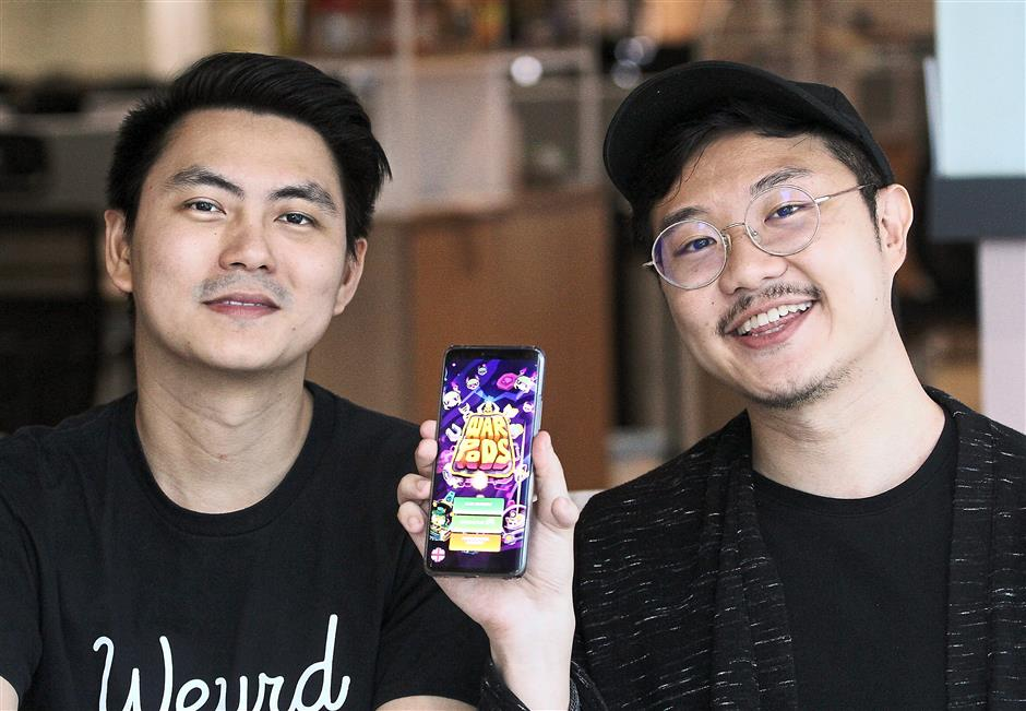 Weyrdworks co-founders Beck (left) and Yean are looking forward to making smaller games, similar to their successful 'WarPods', next year. — AZLINA ABDULLAH/The Star
