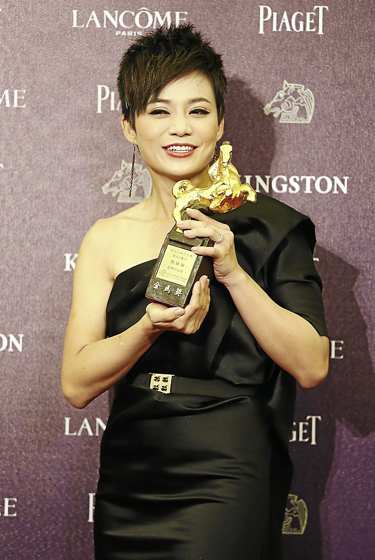 Singapore's actress Yeo Yann Yann, holding her trophy, poses for media for Best Supporting Actress at the 50th Golden Horse Awards in Taipei, Taiwan, Saturday, Nov. 23, 2013. (AP Photo/Wally Santana)