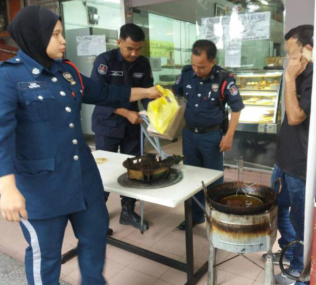 DBKL enforcement officers confiscating the items from the outlet operator who put up cooking items on the sidewalk.
