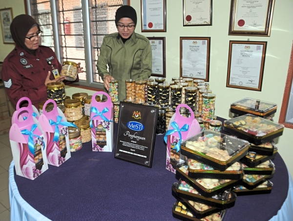 Sjn Azizah (left) and Fatonah inspecting some of the packed  kuih raya and cookies baked for sale by the female inmates of the Alor Setar Prison in Kedah.