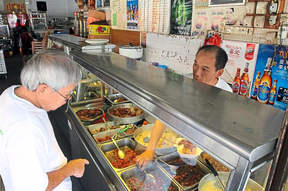 What can I get you: Hung (right) serving a customer at his economy rice stall in Restoran Chung Wah in Ipoh.
