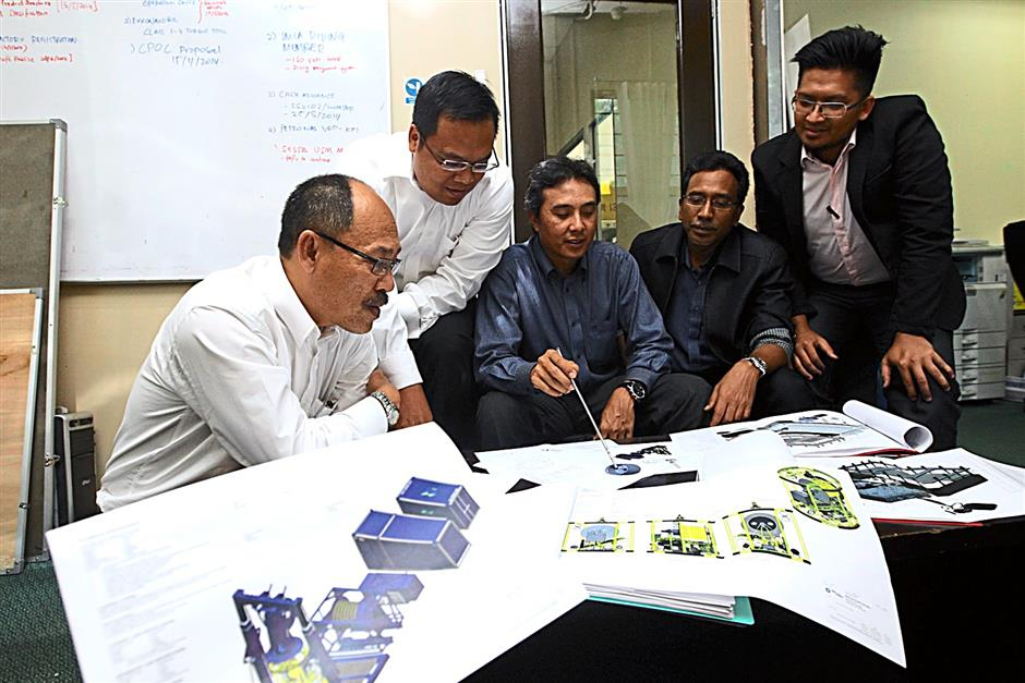 Hazali (centre) and his technical staff reviewing the design of an underwater ROV.An experienced engineer is needed to operate the underwater ROV controller.Subsea employees discussing the potential markets to operate their underwater ROV in complementing the local oil and gas industry.An underwater ROV can be fitted with a wide range of devices such as camera, sonar and other visual and acoustic equipment to complement a dive. - Photos by NORAFIFI EHSAN