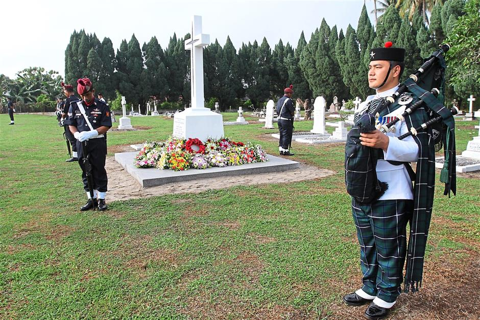 Pipers performed a lament as guests places their wreaths at the annual Remembrance Day held at the Gods Little Acre Cemetery in Batu Gajah.
