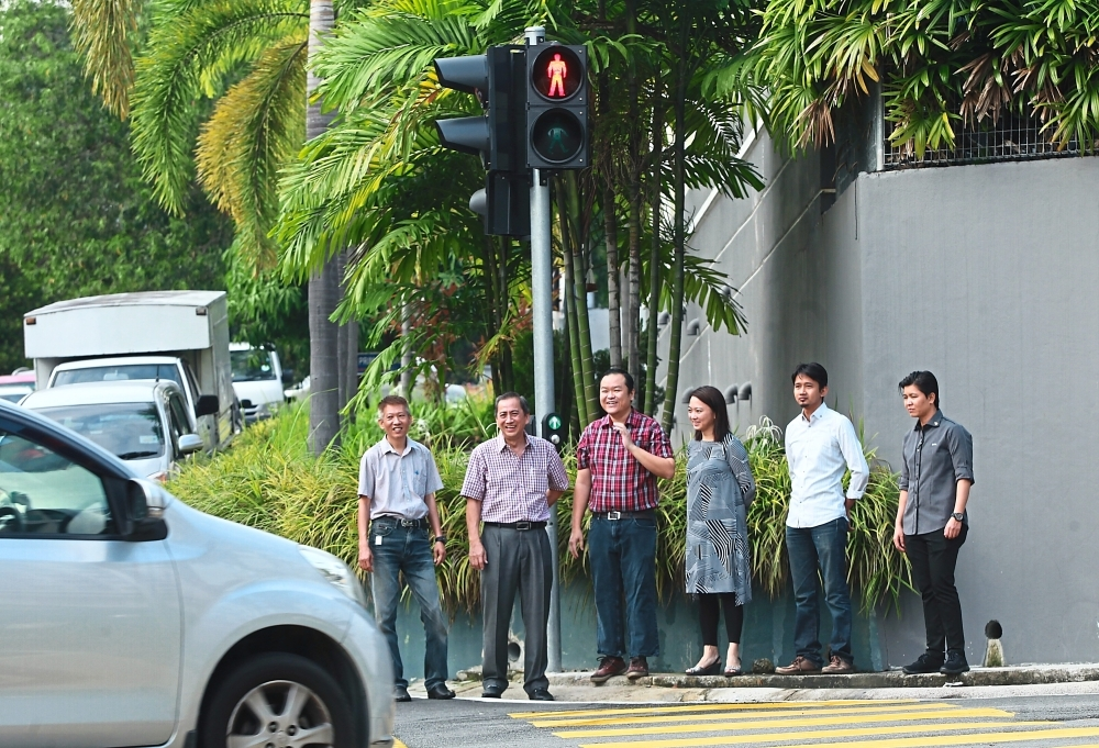 Yeoh (second from right) checking out the newly installed traffic lights with residents.