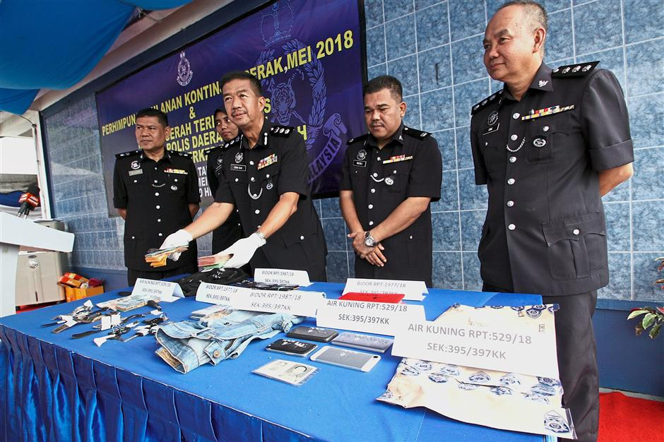 Acp Som sak Din Keliaw (3rd left),the newly appointed Tapah ocpd Superitendent Wan Azharudin Ismail (2nd left) and officers showing the robbery items that were seized in Bidor during a press conference at Tapah police headquarters.