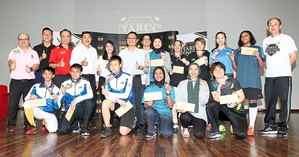 Winners of the TARUC Fencing Open Men's Epee and Women's Sabre with officials from the university during the closing ceremony. (Left) Teammates under the Blade Fencing KL banner, Chornnasun Mayakarn (right) duelling with Shaun Lau in the Men's Foil category final. — Photos: SAMUEL ONG/The Star