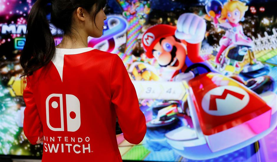 An event employee of Nintendo attends the presentation ceremony of its new game console Switch in Tokyo, Japan January 13, 2017. Picture taken January 13, 2017. REUTERS/Kim Kyung-Hoon