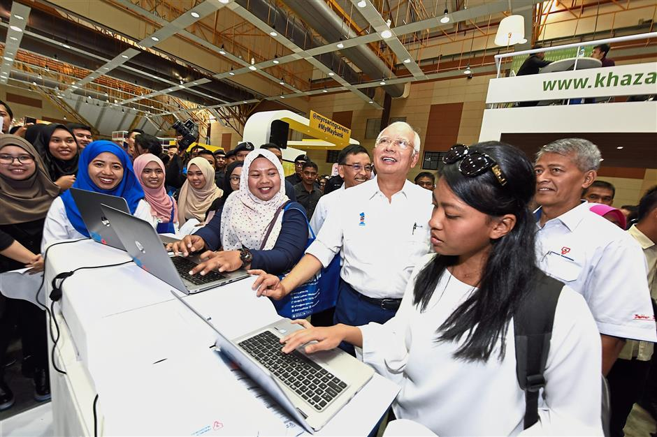 Prime Minister Datuk Seri Najib Tun Razak and aspiring SL1M-IBE trainees are given a walk-through of TNBs SL1M training highlights by Azman Mohd (right) and Muhammad Razif (fourth from right).