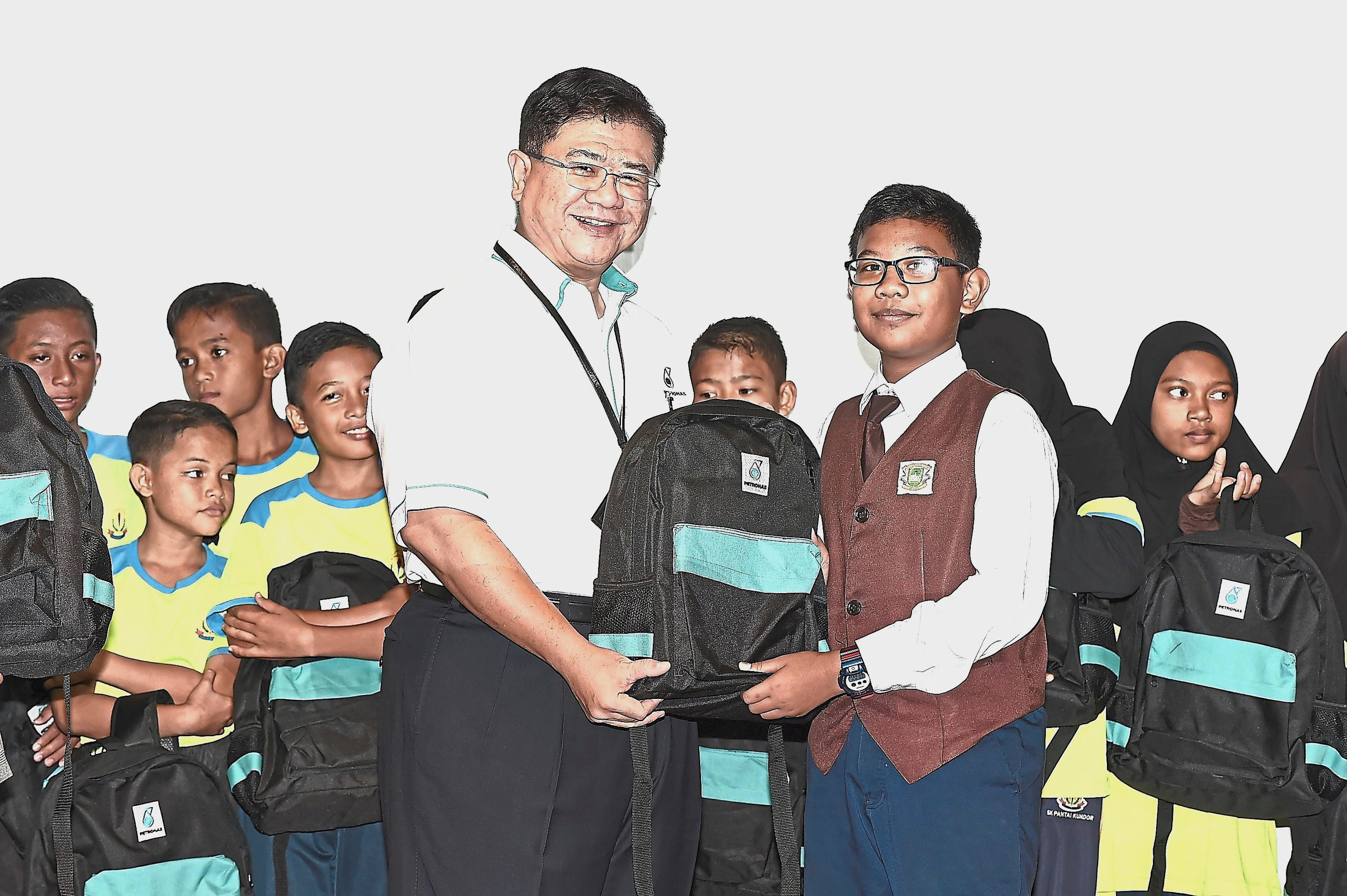(Above) Students receiving school necessities in conjunction with Petronas' Back to School programme.