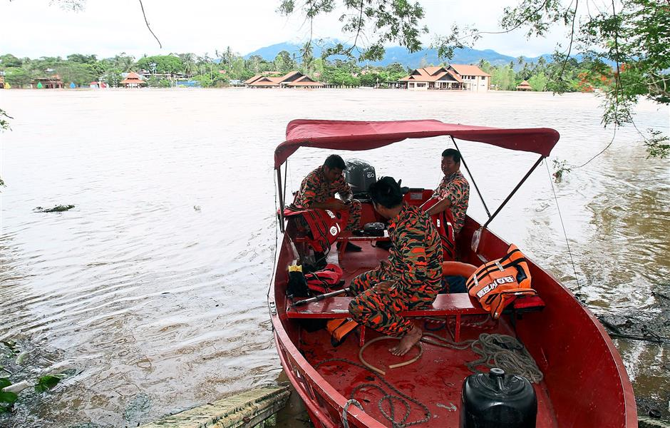 Fire and Rescue Department personnel preparing to evacuate flood victims along the Sungai Perak riverbank in Kuala Kangsar. In the background is the flooded Pesisir Sayong recreation centre.   SAIFUL BAHRI/The Star