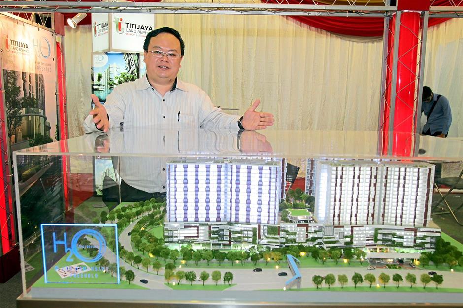 Strong interest: Kelvin Tang, sales manager of Titijaya Land Bhd at his company's booth.