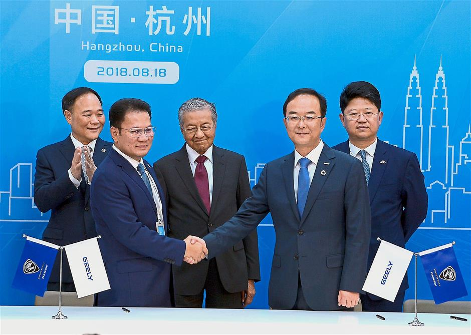 Momentous occasion: Dr Mahathir witnessing the signing of the agreement between Syed Faisal (second, left) and President of Zhejiang Geely Holding Group An Conghui (second, right) at Geely headquarters in Hangzhou, China. — Bernama