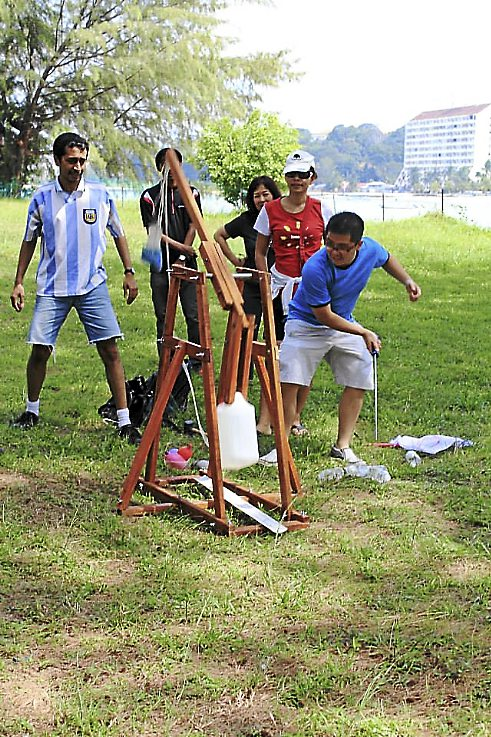 MAIN PIX ON PAGE 15: Fire in the hole: Building a trebuchet that actually was able to catapult water balloons gave us a chance to exercise our living skills and then magically made us all kids again when 'war' was declared! --  Photos from GlobalKnox