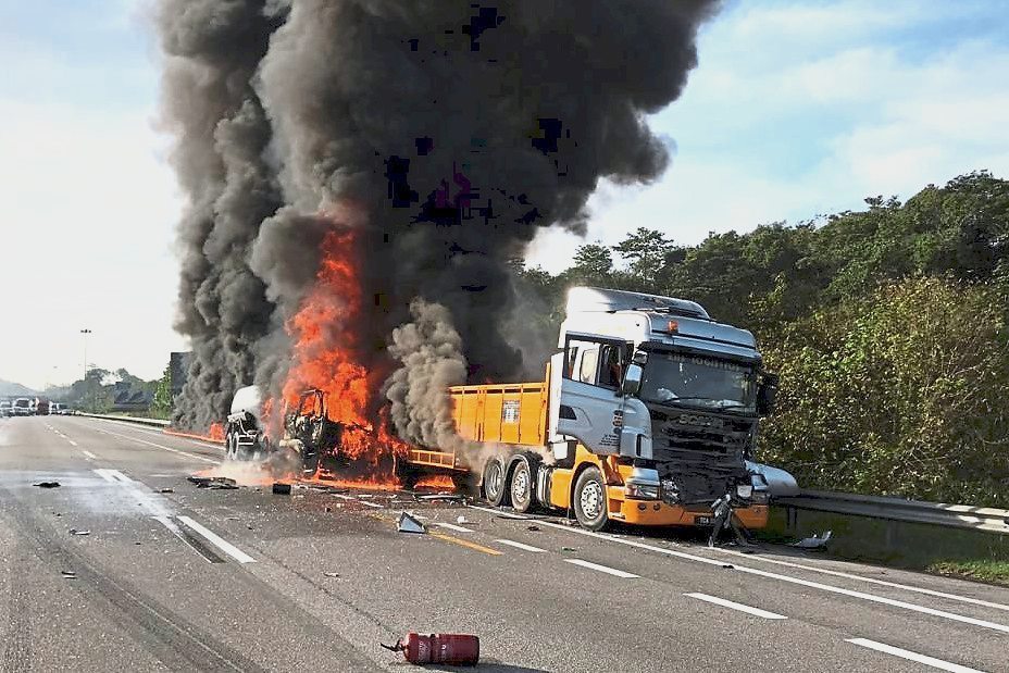 Tragedy on the road: The fiery scene of the accident near Slim River where the fire started between the tanker and the lorry in the middle.