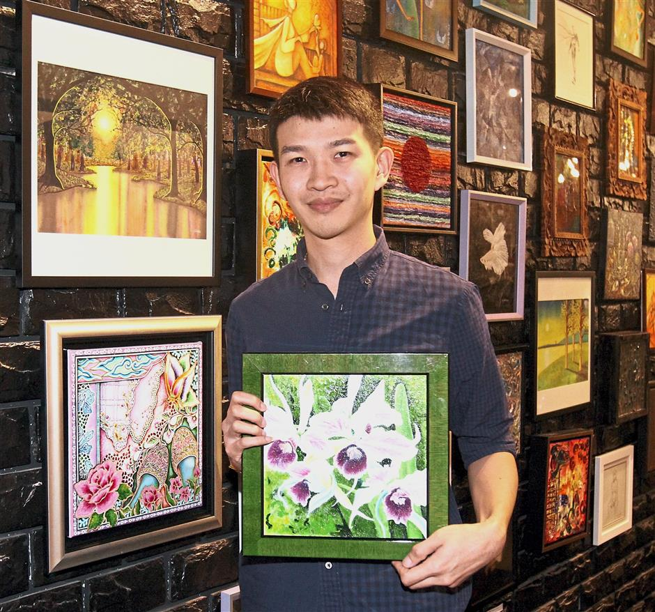 Ng, with one of his paintings exhibited at the gallery. The painting is inspired by orchids in his grandmother's garden.