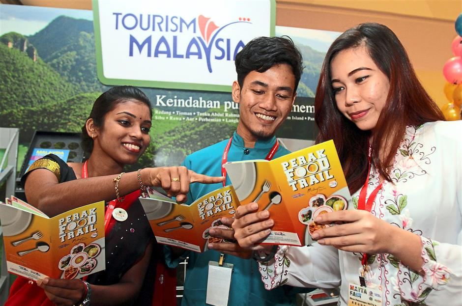Food galore: (From left) S. Shammene Dewy, Muhd Adam Samad Sarifudin and Azni Fazlin Zaini browsing through the Perak Food Trail booklets.
