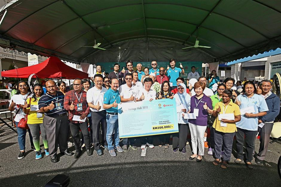 Participants braving the downpour to complete the FMM-OCBC Heritage Walk in Beach Street, Penang. (Right) Chow (centre), VIPs and state officials holding a mock cheque for RM500,000 in aid of various charitable organisations in the state. — Photos: CHAN BOON KAI/The Star