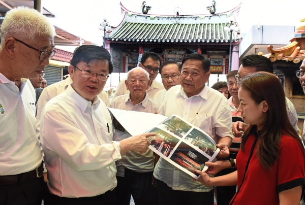 Chow (second left) with state exco member Phee Boon Poh (left) and Berapit assemblyman Heng Lee Lee (right) looking at photos of the Hock Teck Cheng Sin Temple in Jalan Pasar that was damaged in a fire.