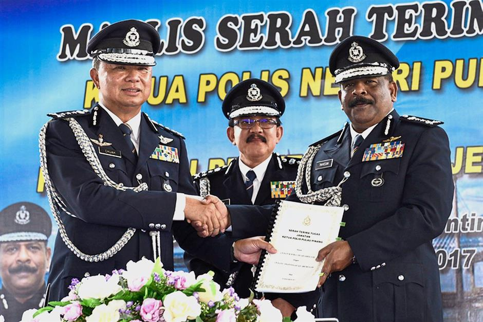 Bukit Aman Integrity and Standards Compliance Department director Comm Datuk Seri Abdul Rahim Hanafi (centre) witnessing the handing over of duties ceremony between the outgoing Penang police chief Comm Datuk Wira Chuah Ghee Lye (left) and incoming state police chief Comm Datuk A. Thaiveegan (right) at Penang police headquarters in Penang Road.Pix by GARY CHEN/The Star/ 29 December 2017.