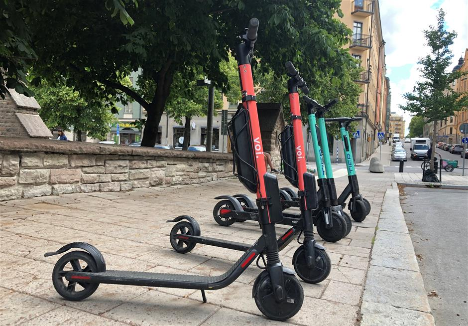 Electric scooters from Swedish startup VOI and Belin-based Tier sit parked side-by-side in Stockholm, Sweden July 7, 2019. Picture taken July 7, 2019. REUTERS/Esha Vaish