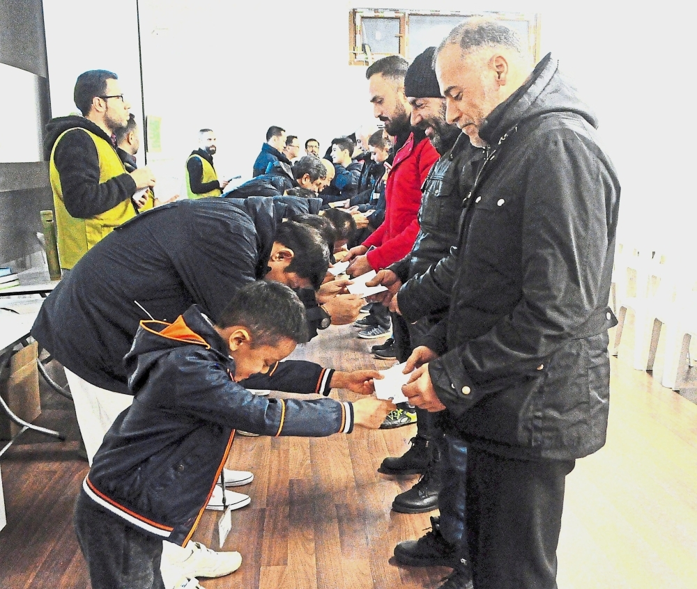 Zhi Hong (left forefront), joins a row of Tzu Chi volunteers to hand over envelopes containing prepaid grocery cards to Syrian refugee families. Volunteers are required to bow low as a sign of thanks to their beneficiaries for giving them the chance to do charity.