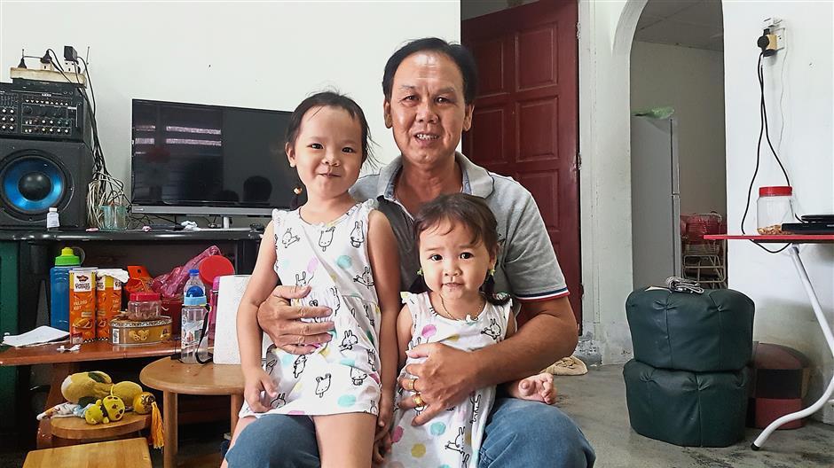 Lim Pak Thong with his two daughters; Chui Yuet, five (left) and Chui Tian, two, at their home in Kampung Tersusun Taman Merdeka in Mambang Diawan, Kampar.