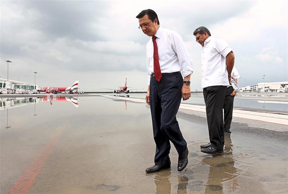 Check-up: Liow (left) inspecting the waterlogged tarmac of the taxiway with Badlisham during his visit to KLIA2 in Sepang. — MOHD SAHAR MISNI / The Star