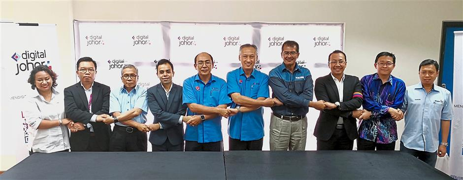 (From left) Aidah, Rosli, Ismail, Shivaji, Abdul Wahab, Abdul Razak, Ramlee, Ahmad Nasri, TM Johor Strategic Economy Corridor general manager Nazri Edham, and Khaidzir linking hands in a symbolic gesture of their partnership and commitment to help Johor develop its digital agenda.