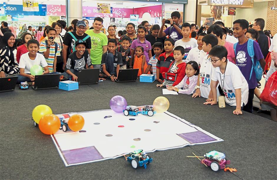 (Above) Pupils showing off their inventions for the Young Innovate Junior competition. (Right) Participants of the Battle Of The Bots competition giving their best shot as onlookers cheer them on.
