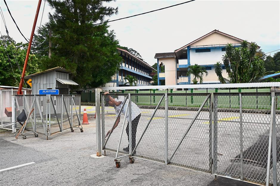 A guard closing a gate at Jalan Pudina which is located next to a school, which cause traffic congestion.
