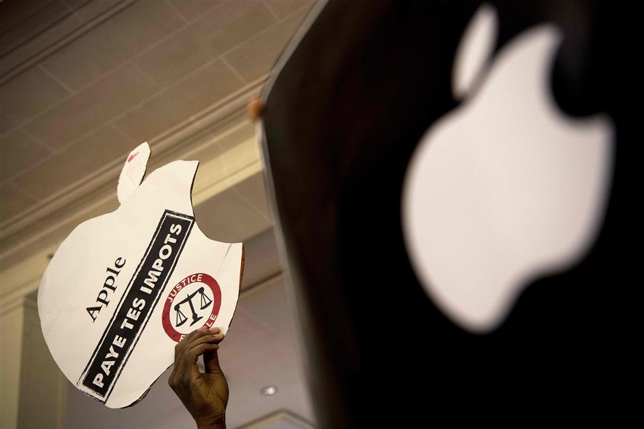 An activist of the Association for the Taxation of Financial Transactions and Citizen\'s Action (ATTAC) holds up a sign of US multinational technology company Apple\'s logo dring a protest against tax evasion at an Apple store in Paris on December 2, 2017. / AFP PHOTO / CHRISTOPHE ARCHAMBAULT