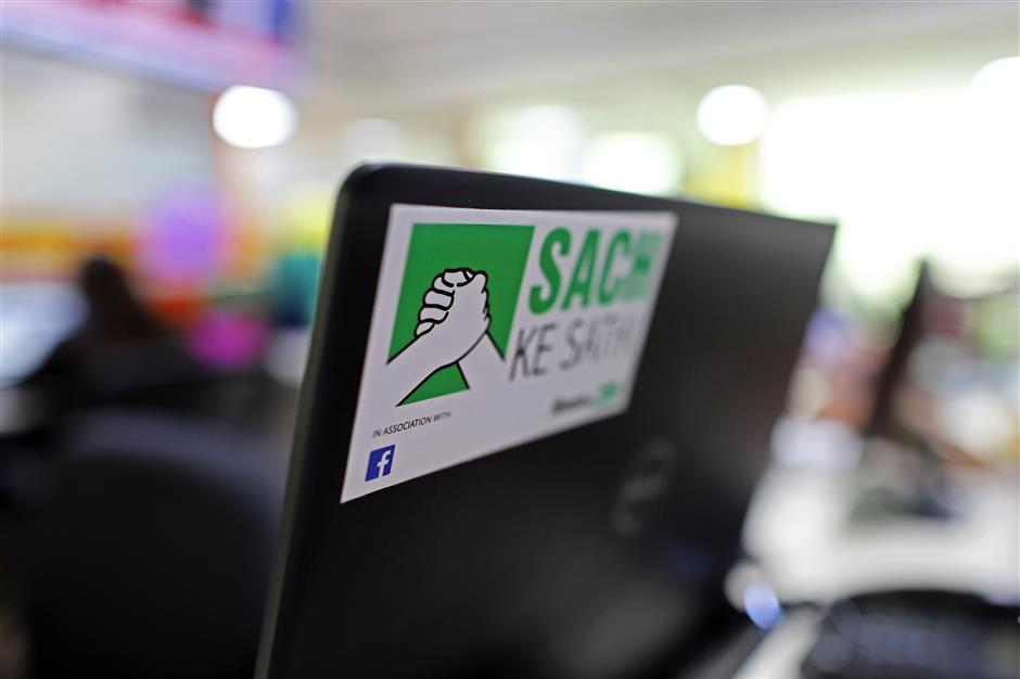 A promotional sticker for Vishwas News, operated by Jagran New Media, reads 'Sach Ke Sathi' which translates as 'Friends of Facts' is displayed on a laptop computer at the Vishwas office in New Delhi, India, on Friday, May 17, 2019. Facebook, Twitter Inc. and Google parent Alphabet Inc. are discovering the harsh reality that disinformation and hate speech are even more challenging in emerging markets than in places like the U.S. or Europe. Vishvas, Facebook's largest Indian-language fact-checking contractor, faces the challenge of working in country with 23 official languages. Photographer: Anindito Mukherjee/Bloomberg