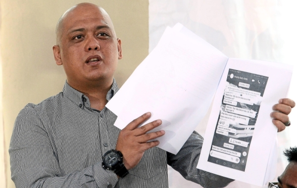 Telling his story: Blission holding printouts of WhatsApp messages screencaptures during a press conference at Bangsar.