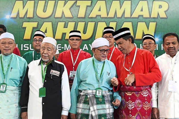 Meeting of minds: Abdul Hadi (front row, middle) talking to Mohamad at the 65th annual PAS muktamar in Kuantan. u2014 Bernama