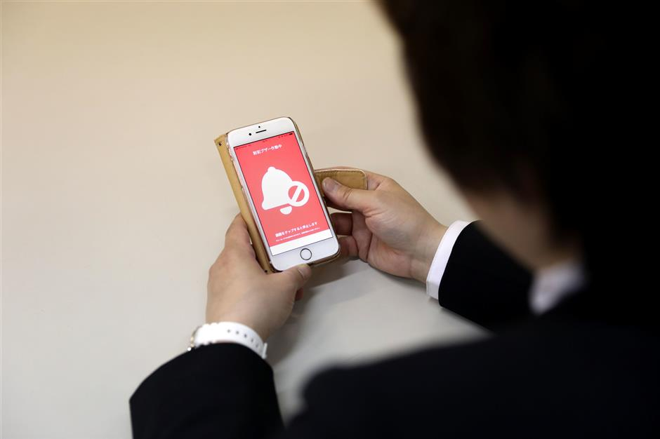 In this picture taken on May 13, 2019, an official at a police department poses as she shows an application for scaring off molesters, in Tokyo. - A Tokyo police smartphone app to scare off molesters has become a smash hit in Japan, where women have long run the gauntlet of groping on packed rush-hour trains. Victims of groping can activate the Digi Police app, which either blasts out a voice shouting 'stop it' at top volume or produces a full-screen SOS message reading: 'There is a molester. Please help.' (Photo by Behrouz MEHRI / AFP)