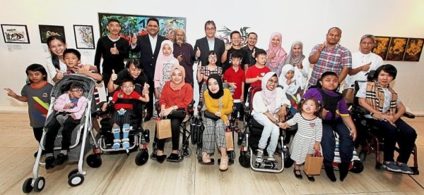 Wan Marzimin (back row, fourth from left) and Shahril Azuar (second from left) together with guest artists and children at the The Art for SMA-LL exhibition.