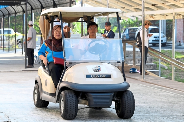 Alternative transport: An EC staff member driving a disabled voter to the polling centre at SK Muhibbah. — Bernama