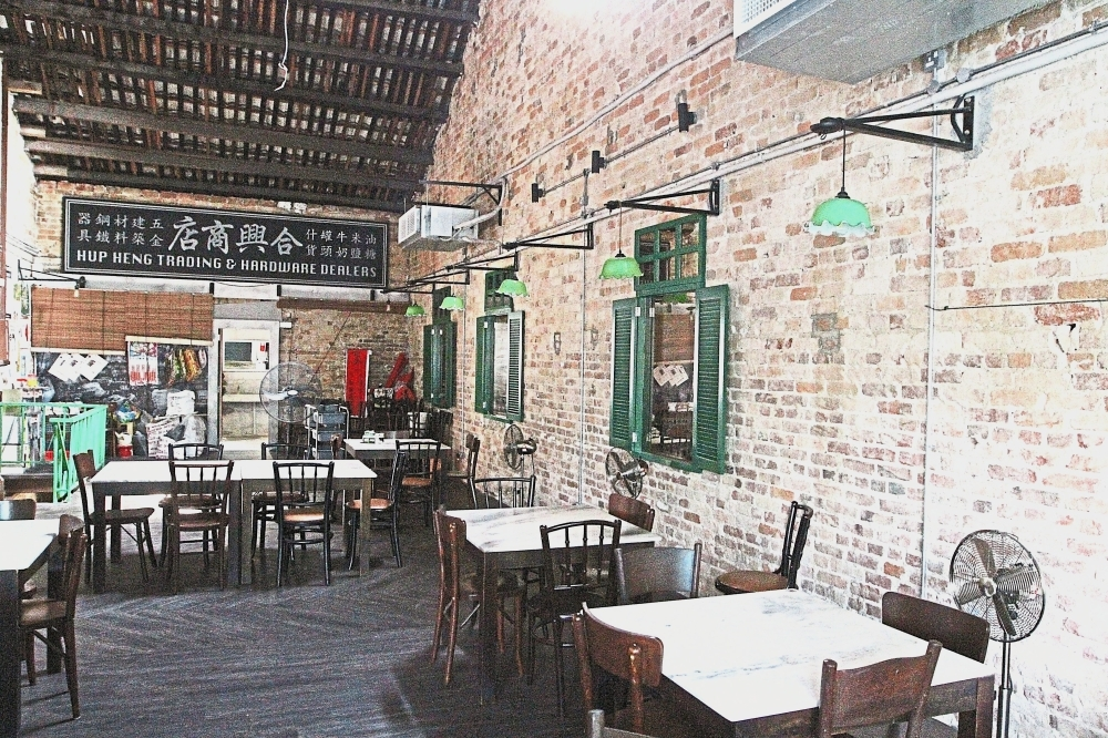 The second level of Ho Kow Hainan Kopitiam is filled with old tables and items from the past.