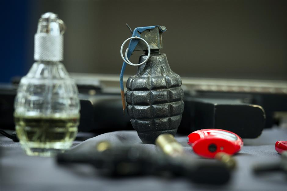 An inert hand grenade is seen along with other banned items taken from passengers at Transportation Security Administration (TSA) checkpoints at Dulles International Airport in Dulles, Va., Tuesday, March 26, 2019. TSA's social media presence has been something of a model for other federal agencies _ striking a tone is humorous, but still gives travelers informational dos and don'ts.(AP Photo/Cliff Owen)