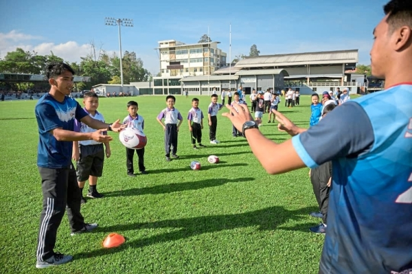 The children learning the basics of rugby.