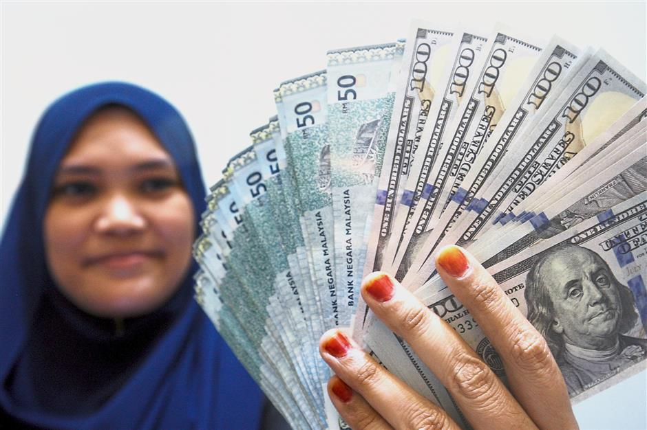 A teller, Rozana Delrosario showing some ringgit note and US dollar note on the story of ringgit up verses US Dollar at Bangsar, Kuala Lumpur. FAIHAN GHANI/The Star.
