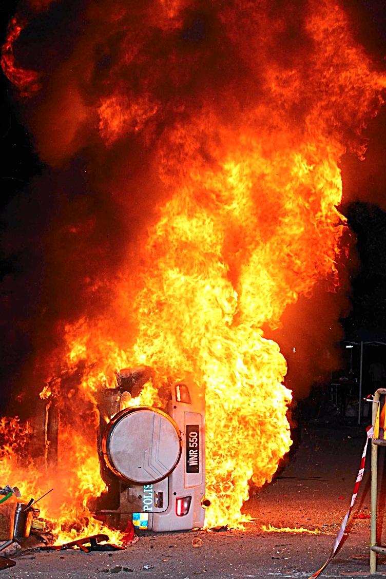 Raging flames: A police car set ablaze after the match at Sarawak Stadium. - ZULAZHAR SHEBLEE / The Star
