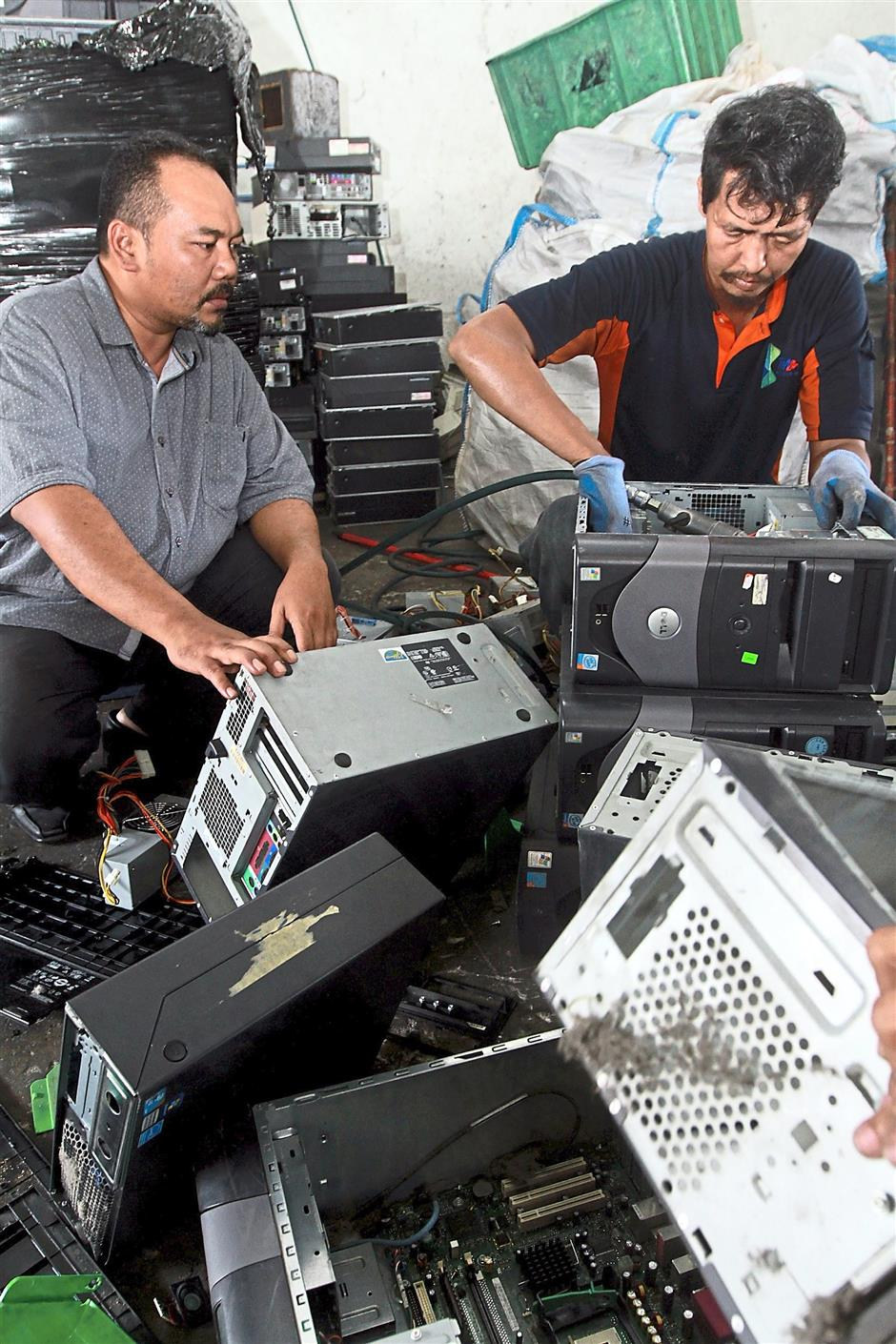 Syamsul (left) says that the company won't junk any computers that can be fixed and resold. — K.K. SHAM/The Star