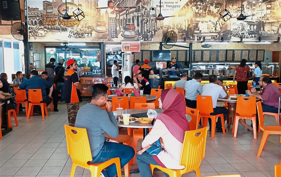 People having lunch at Nasi Vanggey restaurant. The eatery's proprietor says he will be able to maintain the food prices here.