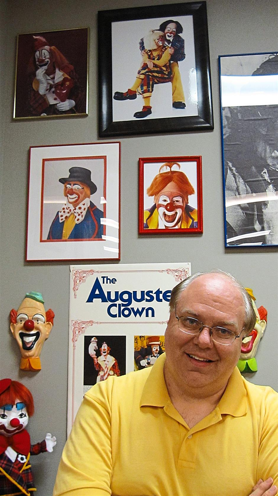 Inside the International Clown Hall of Fame. Its executive director Greg DeSanto (right) is a former Ringling Brothers clown; his wife, also a clown, is pictured in the highest photo above his head.