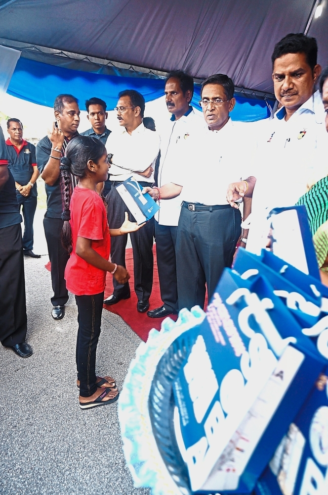 Former health minister Datuk Seri Dr S. Subramaniam presenting goodie bags put together by Maxvue Vision for underprivileged children at a charity event.