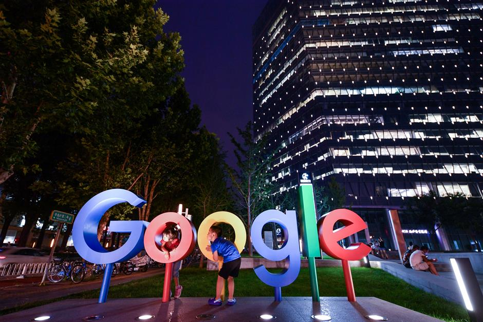 Children play around a sign of Alphabet Inc\'s Google outside its office in Beijing, China August 7, 2018. Picture taken August 7, 2018. REUTERS/Stringer  ATTENTION EDITORS - THIS IMAGE WAS PROVIDED BY A THIRD PARTY. CHINA OUT.    REUTERS/Stringer