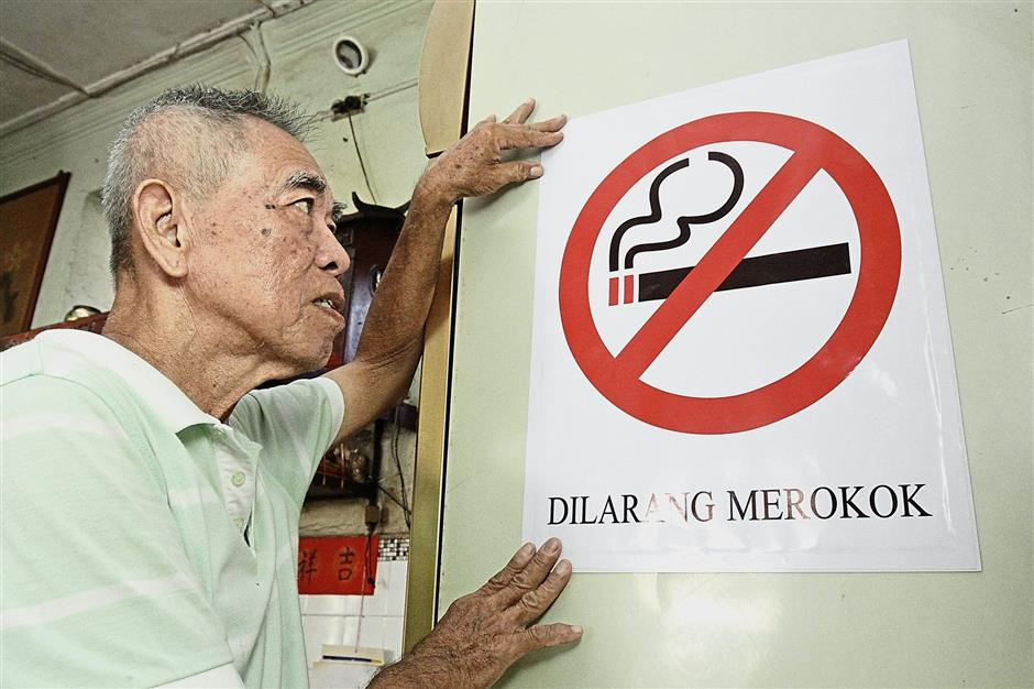 Teoh putting up a no-smoking sign at his coffee shop. He says his customers have expressed displeasure over the ban.
