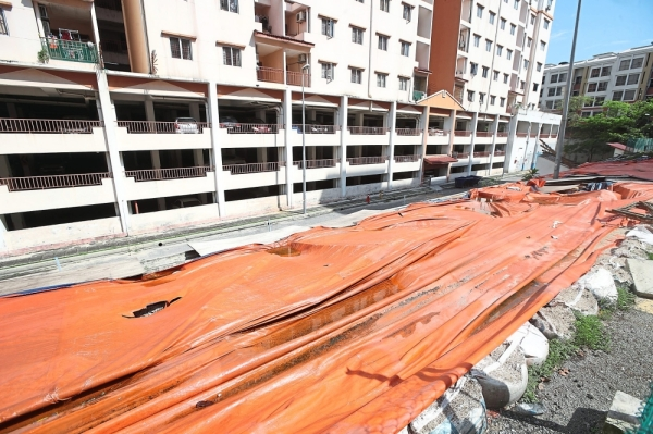 The area where the retaining wall collapsed has been covered with plastic sheets to prevent soil run-off after heavy rain.